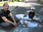 Modesto and his son drawing with sidewalk chalk.